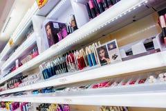 Parfums en schoonheidsmiddelen op de planken bij drogisterij Stock Foto