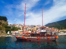 Parga city, greek summer tourist resort with colorful houses and sailing boat with tourists