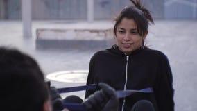 Pargenomkörare utomhus Slut upp av latin - den amerikanska kvinnliga hållande motståndsmusikbandet med hennes hjälpande tillbaka  lager videofilmer