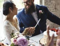 Parhänder som rymmer bröllopstårtakniven Royaltyfria Foton