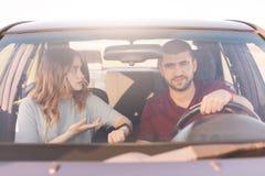 Parhandelsresande når destinationen med bilen, berättar den härliga kvinnan somethig hennes make på hjulet, medan sitta på framsä royaltyfria foton