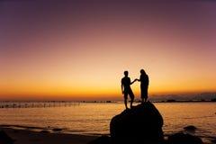 Parhanden - in - räcka den hållande ögonen på soluppgång och solnedgången Arkivfoton