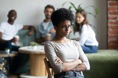 Paria negro de la muchacha que se sienta aparte de pares en cafetería fotografía de archivo