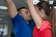 Paridrottsman nen Doing Pull Ups i idrottshall fotografering för bildbyråer