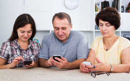 Parientes que usan los teléfonos móviles Imagen de archivo libre de regalías