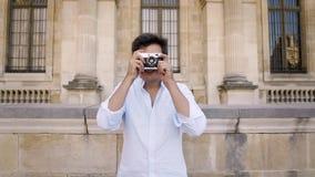 Parigi, Francia, aprile 2019 Giovane in camicia bianca che fa foto con una macchina da presa sul fondo del museo del Louvre archivi video
