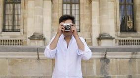 Parigi, Francia, aprile 2019 Giovane in camicia bianca che fa foto con una macchina da presa sul fondo del museo del Louvre stock footage