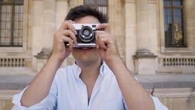 Parigi, Francia, aprile 2019 Giovane in camicia bianca che fa foto con una macchina da presa sul fondo del museo del Louvre video d archivio