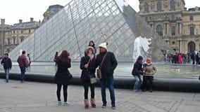 PARIGI, FRANCIA - 31 DICEMBRE, 2016 Coppie che fanno i selfies vicino al Louvre, al museo francese famoso ed al turistico popolar Fotografia Stock