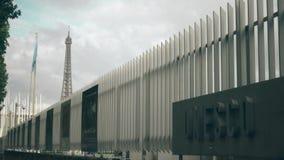 PARIGI, FRANCIA - 8 OTTOBRE 2017 La bandiera d'ondeggiamento ed il segno dell'Unesco imbarcano contro la cima della torre Eiffel stock footage