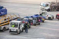Parijs, Frankrijk - april 2016: Arbeider die bagage op aanhangwagen van transportband op baan stapelen die naar vervoersauto gaan royalty-vrije stock foto's