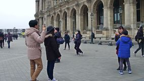 PARIJS, FRANKRIJK - DECEMBER, 31, 2016 Aziatische toeristen die en foto's dichtbij het Louvre, beroemd Frans museum stellen maken Stock Fotografie