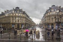 PARIJS, FRANKRIJK - MAART 25, 2014: Mensen met gekleurde paraplu's in de straten op een regenachtige dag op de straten van Parijs Royalty-vrije Stock Foto's