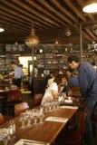 Parijzenaars en de toeristen brengen gelukkig uur in een koffiebar door Stock Fotografie
