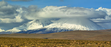 Parinacota and Pomerape volcanoes. View of snow-capped Parinacota and Pomerape volcanoes known as Payachatas, Chile Royalty Free Stock Images