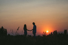 Parinnehavhänder på solnedgångbakgrund Royaltyfria Foton