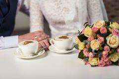 Parinnehavhänder som älskar par som dricker kaffe i ett kaffe Royaltyfri Foto