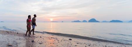 Parinnehavhänder som går på stranden på solnedgången, den unga turist- mannen och kvinnan på havsferie arkivfoton