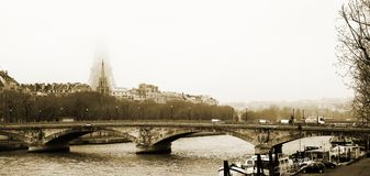 Paris #8. Bridge in Paris, France. Eiffel Tower just visible in the fog.  Movement on cars driving. Gloomy winters day. Copy space, Sepia Tone Royalty Free Stock Image