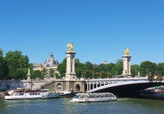 Paris, Alexandre Bridge. Alexandre Bridge with boats on the Seine river and the dome of the Petit Palais in the background, Paris, France Royalty Free Stock Photography
