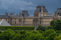 Paris 2. Angled view of the Louvre from a distance nice green treeline foregroung blue sky background Royalty Free Stock Photo