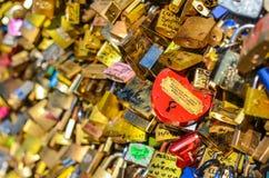 PARIS - APRIL 2014: Förälskelsehänglås på Pont des Arts på April 17, 2014, i Paris, Frankrike Massor av färgrika lås på a Arkivbilder