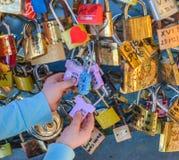 PARIS - APRIL 2014: Förälskelsehänglås på Pont des Arts på April 17, 2014, i Paris, Frankrike Massor av färgrika lås på a Arkivfoton