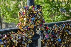 PARIS - APRIL 2014: Förälskelsehänglås på Pont des Arts på April 17, 2014, i Paris, Frankrike Massor av färgrika lås på a Arkivbild