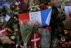 PARIS ATTACKED. Copenhagen/Denmark/ _ 15th November  2015 _French flag at half mast at french Embassy in Copenhagen and Danish police presentspeople laying Stock Images