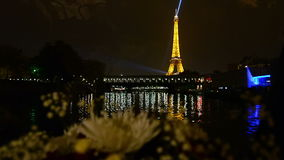 Paris by boat. Seine river point of view from beautiful restaurant boat approaching the Eiffel Tower at night in Paris, France stock video