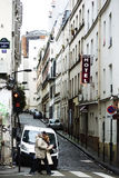 Paris Boulevard de Clichy. Paris, France - January 1, 2014: Two old people pass a side street with a traffic light and a hotel in the Montmartre district of Stock Images