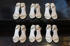 The bride's shoes and the bridesmaids`s shoes on the black wooden floor royalty free stock photography