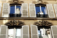 Paris building facades with white shutters. And carved faces, ornaments, situated between Ile de la Cité and the Latin Quarter. Latin district in the heart royalty free stock photo