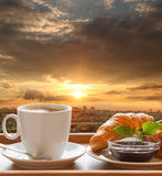 Paris cafe with croissants against sunset over city in France Stock Photography
