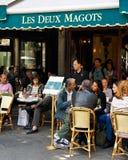 Paris Cafe. Paris, France - July 14, 2011 - Diners enjoy the outdoors at the famous Les Deux Magots cafe in Paris. The cafe lifestyle draws millions of tourists Stock Photos