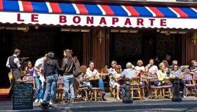 Paris Cafe. Paris, France - July 14, 2011 - Diners enjoy the sun at the Bonaparte Cafe in Paris. The cafe lifestyle draws millions of tourists to Paris each year Stock Photos