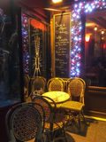 Paris cafe table on a winter night, with menu chalked on a board outside Royalty Free Stock Photo