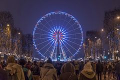 Paris Champs Elysee Ferris wheel. New year celebration crowd walking up from the Champs Elysées to Concorde place and the Ferris wheel at night, Paris stock photography