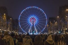 Paris Champs Elysee Ferris wheel. New year celebration crowd walking up from the Champs Elysées to Concorde place and the Ferris wheel at night, Paris, France royalty free stock images
