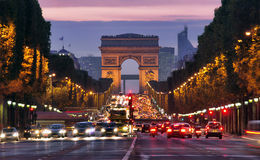 Champs-Elysees Avenue with traffic Arc de Triomphe in Paris France at night. car traffic with many cars on the street