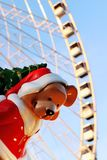 Paris Christmas bear under the Ferris wheel place de la Concorde. Paris Christmas bear, santa style, under the Ferris wheel place de la Concorde. Funny, he carry stock image