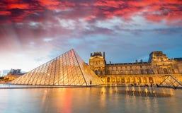 PARIS - 17 DE JUNHO DE 2014: Por do sol bonito sobre o archi do museu do Louvre Fotografia de Stock