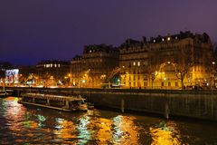 PARIS - DECEMBER 22, 2017: Night traffic in Paris on the boulevard and on the rive. Traffic at night in Paris, boat on the Seine river Stock Image