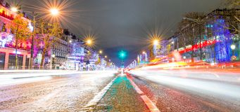 PARIS - DECEMBER 2012: Traffic along Champs Elysees at night in. Paris. The city attracts 40 million people annually Stock Photo