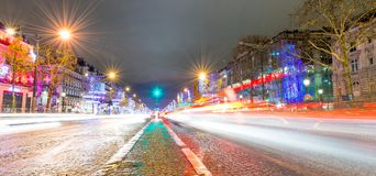 PARIS - DECEMBER 2012: Traffic along Champs Elysees at night in. Paris. The city attracts 40 million people annually Royalty Free Stock Photography