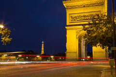 Paris with Eiffel Towe and Arc D'Triomph at night. Evening view of Arc D'Triomph with Eiffel Tower in background, with red streaks of light from moving cars Royalty Free Stock Image