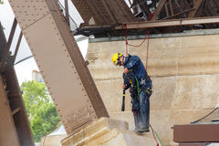 Paris. The Eiffel Tower. Paris, France - May 9, 2014: Man steeplejack washes foundation of the Eiffel Tower Stock Images
