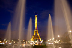 Paris Eiffel tower by night. With lights on seen from between fountains