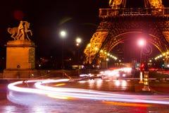 Paris Eiffel Tower Traffic Night. Touristic spot and landmark in Paris, France: a street near the Eiffel tower Tour de Eiffel by night with cars, streetlights Stock Photo