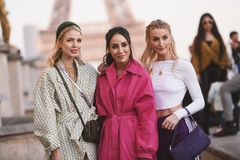 Paris Fashion Week - street style - PFWAW19. Paris, France - February 27, 2019: Street style outfit - Fashionable girls posing in front of Eiffel Tower during stock image